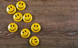 Yellow emoticon icons on wooden background top view. Emoticon icons on wooden background top view royalty free stock photography