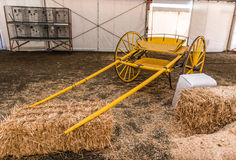 Yellow empty carriage sits near hay bales Royalty Free Stock Photography