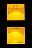 Yellow empty shelves for exhibit in the black wall Royalty Free Stock Image