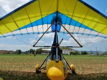 Yellow engine hang glider. Faicchio, Campania, Italy - 10 June 2018: Two-seater motorized hang glider on display at Macchia on the occasion of the first edition royalty free stock photography