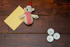Yellow envelope with candles and bear. Yellow envelope, Christmas bear and three candles on the wooden table royalty free stock image