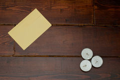 Yellow envelope with candles. Yellow envelope and three candles on the wooden table stock images