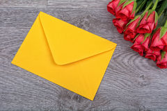 Yellow envelope and roses on a wooden background. Yellow envelope and red roses on a wooden background stock photos