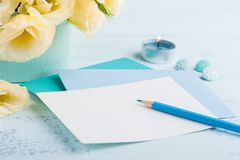 Yellow eustoma flowers and envelope. On blue table. Greeting card for Birthday, Womens or Mothers Day Stock Photo