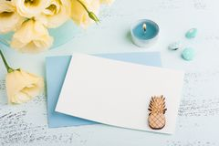 Yellow eustoma flowers and envelope on blue table. Greeting card for Birthday. Womens or Mothers Day Royalty Free Stock Image