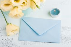 Yellow eustoma flowers and envelope. On blue table. Greeting card for Birthday, Womens or Mothers Day Stock Images