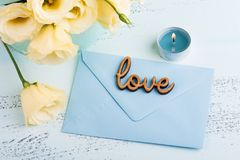 Yellow eustoma flowers and envelope. With sign love on blue table. Greeting card for Birthday, Womens or Mothers Day Stock Image