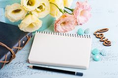 Yellow eustoma flowers and open notebook. On blue table. Greeting card for Birthday, Womens or Mothers Day Royalty Free Stock Image