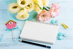 Yellow eustoma flowers and open notebook. On blue table. Greeting card for Birthday, Womens or Mothers Day Stock Photos