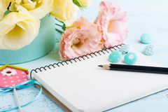 Yellow eustoma flowers and open notebook. On blue table. Greeting card for Birthday, Womens or Mothers Day Royalty Free Stock Photo