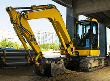 Yellow excavator. Under a building in Paris Royalty Free Stock Photography