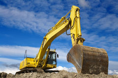 Yellow excavator. Work in blue sky Royalty Free Stock Images