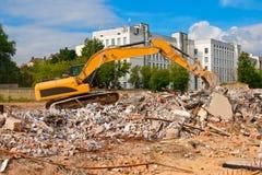 Yellow excavator. Working on dismantling brick building Stock Photos