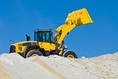 Yellow excavator. A yellow excavator working on sand, blue sky in the background Stock Image