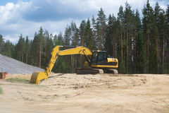 Yellow excavator on the background of heaps of sand Stock Photos