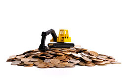 Yellow excavator on a big heap of coins. White background Stock Photos