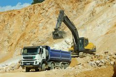Yellow excavator and big truck. Yellow excavator loading stones in a truck Royalty Free Stock Photography