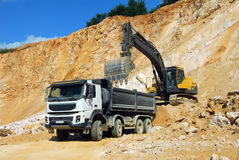 Yellow excavator and big truck. Yellow excavator loading stones in a truck Royalty Free Stock Images