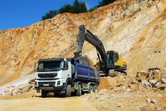 Yellow excavator and big truck. Yellow excavator loading stones in a truck Stock Images