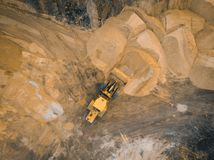 Yellow excavator or bulldozer works on construction site with sand, aerial or top view royalty free stock photography
