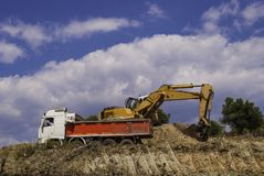 Yellow excavator on the construction site loads the soil into the body of a red dump truck.  stock photography