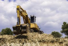 Yellow excavator on the construction site is preparing to load t royalty free stock images
