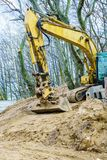 Excavator digging on site in forest environment. Yellow excavator dig digging trench on construction site in forest among trees. Devastation destruction of Stock Image