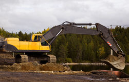 Yellow excavator digging. Crawler excavator working on the roadside Stock Photo