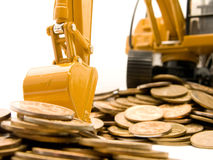 Yellow excavator digging a heap of coins Royalty Free Stock Photography