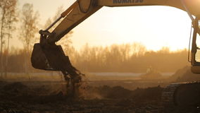 Yellow excavator digging a hole and pours sand. HD stock footage