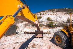 Yellow excavator digging on mountain. On a sunny day royalty free stock photo