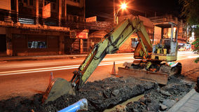 Yellow excavator digging street at night royalty free stock image