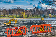 Yellow excavator doing lake cleaning and maintenance services Royalty Free Stock Images