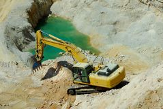 Yellow excavator, dredge. Big yellow loader stands in the quarry Stock Photo