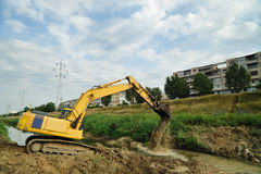 Crawler excavator. Working on riverbed site in town district Royalty Free Stock Images
