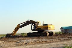 Yellow excavator excavating. On construction site royalty free stock images