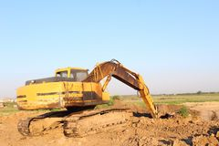 Yellow excavator excavating. On contruction site royalty free stock image