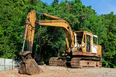 Yellow excavator at the forest. And blue sky Stock Image
