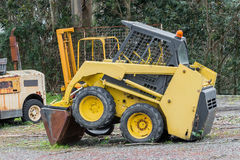 Yellow excavator in a grader parked Stock Photos