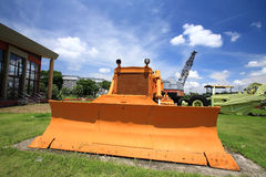 Yellow excavator on the grass. Against blue sky Stock Images