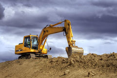 Yellow excavator on a hill Stock Photos