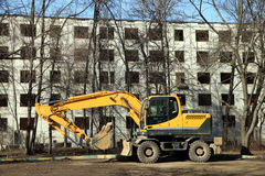 The yellow excavator on housebreaking. The yellow excavator against empty building Stock Photo