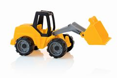 Yellow excavator isolated on white background with shadow reflection. Plastic child toy on white backdrop. Construction vehicle. Children`s toy. Tractor Toy Royalty Free Stock Images