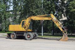 Yellow excavator with a large bucket. On the street Stock Image