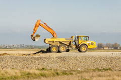 Yellow excavator loading soil on a truck at mine. Stock Photography