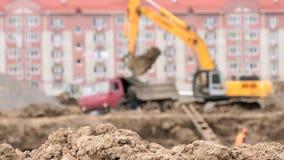 Yellow excavator loads clay using its big bucket stock video