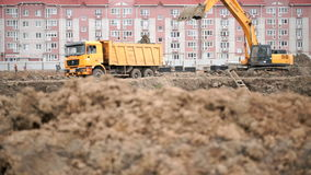 Yellow excavator loads clay using its big bucket stock video footage