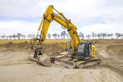 Excavator at a construction site. Yellow excavator at a loamy construction site Royalty Free Stock Photos