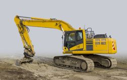 Excavator at a construction site. Yellow excavator at a loamy construction site, partly  in grey back Royalty Free Stock Image