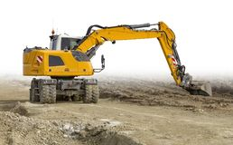 Excavator at a construction site. Yellow excavator at a loamy construction site, partly isolated in white back Royalty Free Stock Images